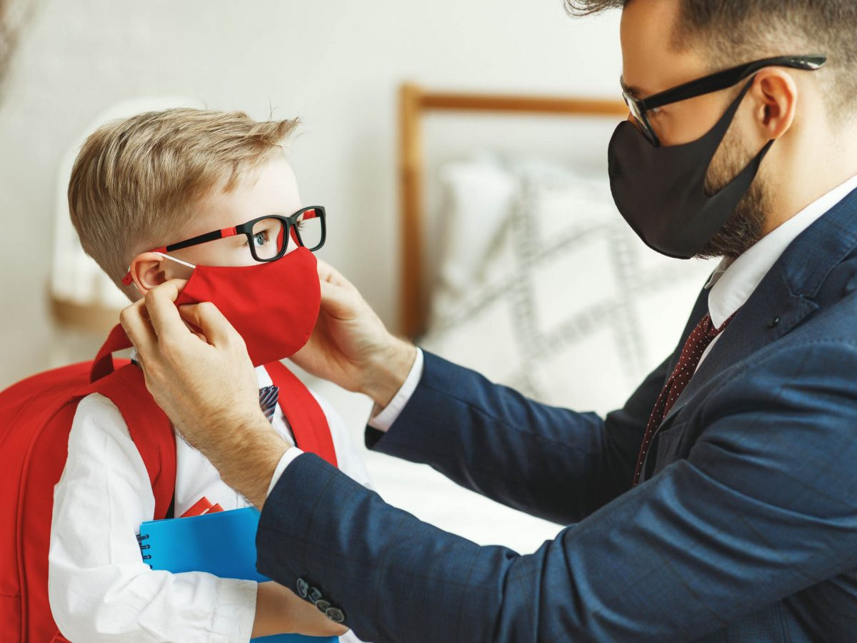businessman father accompanies his son to school putting on a mask to protect and prevent coronavirus