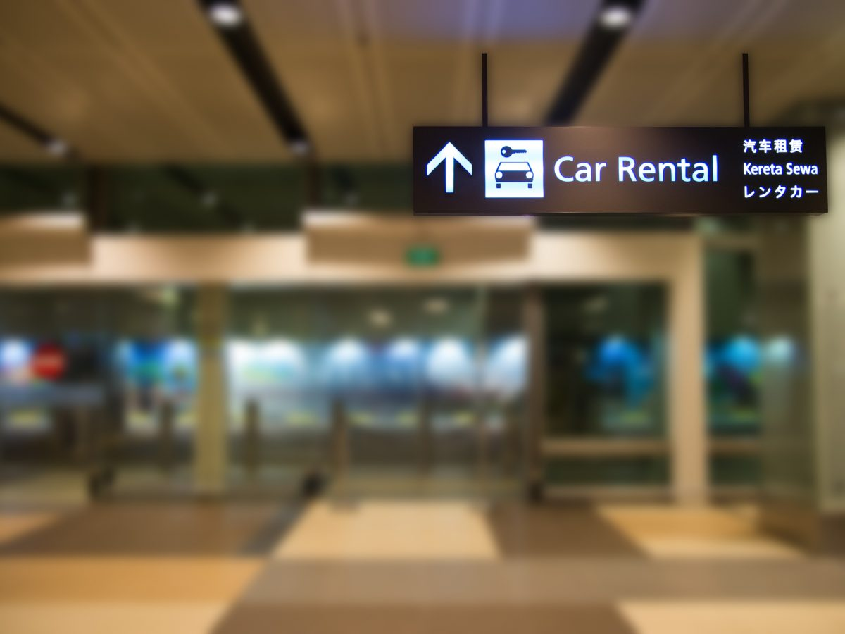 blue illuminated rental car sign with blur background